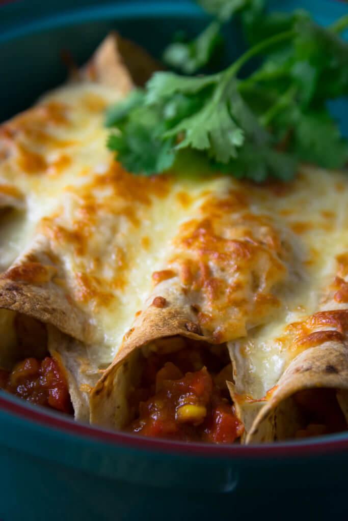 Mit Käse knusprig überbacken, leckere Geflügel Burritos mit Koriander und Guacamole