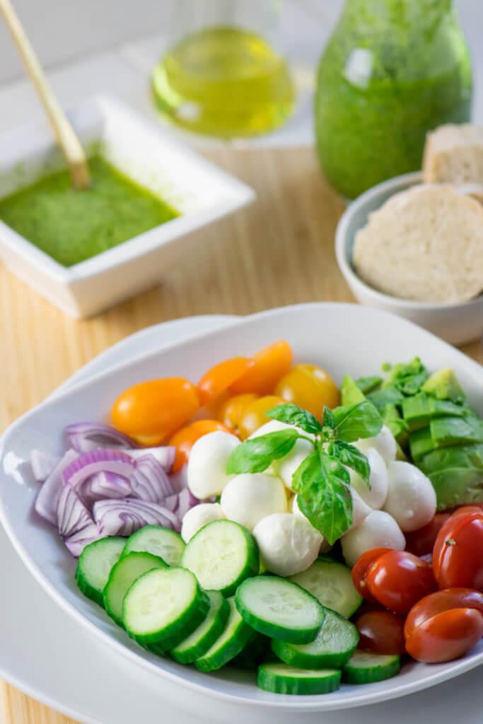 Sommersalat mit Avocado Salat mit Mozzarella, Tomate und Pesto Dressing