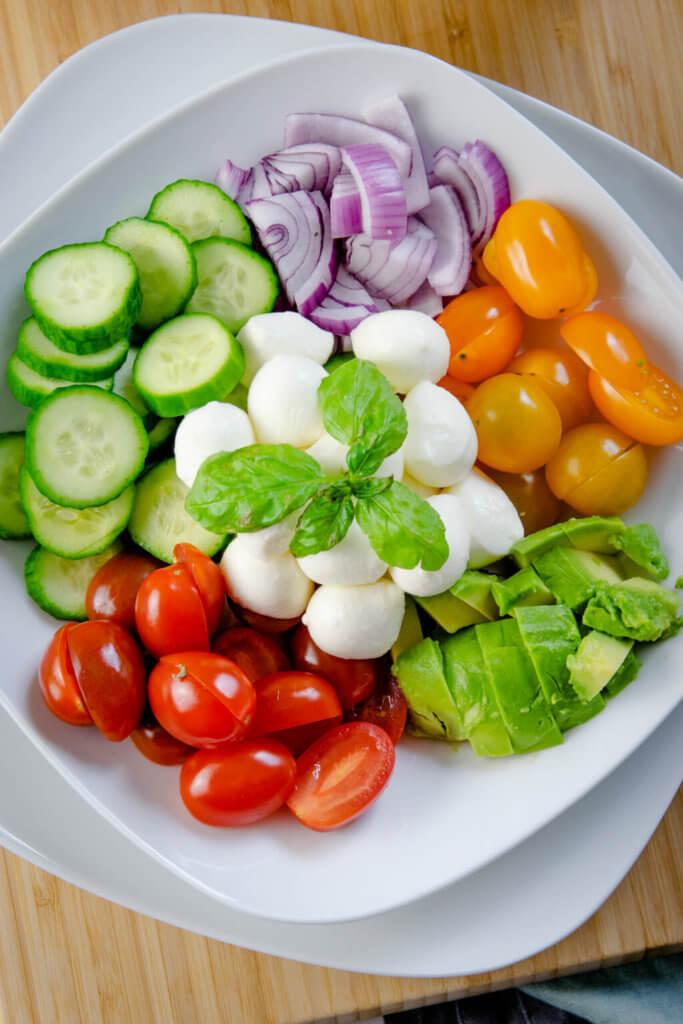 Gurken, Zwiebeln, Tomaten, Avocado und Mozzarella mit Pestodressing