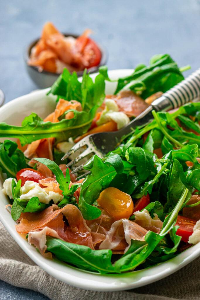 """Der Rucola Salat mit Tomate, Mozzarella und Serrano Schinken gehört zu den besonders einfachen und unkomplizierten Rezepten auf dem Blog und ist absolut köstlich. Dazu gibt es ein ruck zuck Balsamico Dressing und fertig ist der Genuss zum heißen Sommerwetter. Wer mag, kann dazu auch noch frische Honigmelone in den Salat geben. Die Kombi mit dem Serrano Schinken ist der Knaller. Wie du weißt, mag ich es unkompliziert. Ich habe bereits vor einigen Wochen diesen himmlischen Salat zubereitet und fotografiert. In der ersten Hitzewelle im Frühsommer. Leider hat es der Juli bei uns im Norden nicht besonders gut mit uns gemeint und uns keinen echten Sommer gegönnt. Aber jetzt knallt gerade die Sonne wieder vom Himmel und mir ist nach einem köstlichen Salat - leichte Küche ist bei dieser Hitze einfach viel angenehmer. Da ich zuhause die einzige bin, die auf Rucola, Mozzarella und Serranoschinken steht, gibt es heute auch nur die """"einfache"""" Rezeptmenge. Wenn du nun die Menge für 2 oder mehr Personen zubereiten möchtest, brauchst du aber nicht alles verdoppeln - aber du kannst :-) Es reicht pro Person eine halbe Kugel Mozzarella, aber ich wollte keine Reste übrig behalten. Auch das Dressing ist recht großzügig bemessen, wenn ich etwas übrig behalte, stelle ich mein Balsamico Dressing einfach in den Kühlschrank um es am nächsten Tag wieder zu verwenden. Serranoschinken bekommst du in nahezu jeder Wurstabteilung, am besten schmeckt er mir frisch vom Metzger. Aber da ich es unkompliziert mag und oft sehr spontan entscheide, habe ich gerne eine Verpackung Serrano oder Parmaschinken im Kühlschrank liegen. Dieser Rucola Salat ist absolut genial, er schmeckt zu jeder Jahreszeit, ist aber besonders erfrischend im Sommer, wenn es so heiß ist, wie aktuell. Du brauchst nur wenige Zutaten frischer Rucola Kirschtomaten Mozzarella Pinienkerne (optional) Serrano Schinken Balsamico Essig Bianco Olivenöl etwas Salz & Pfeffer In nur 10 Minuten ist dein Salat fertig zubereitet: Wasche zunächst d"""