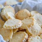Die Heidesand Plätzchen mit Marzipan sind ein echter Klassiker (nicht nur) zu Weihnachten und sehr beliebt. Sie sind super einfach zu backen und schmecken der ganzen Familie. Die Heidesand Kekse werden als Rolle geformt, in Hagelzucker gerollt und dann in Scheiben geschnitten. Dann backst du die Marzipan Plätzchen im Ofen. Nur so lange, dass die schön mürbe sind und auf der Zunge zergehen. Ich stecke total im Weihnachtsfieber und habe direkt wieder gebacken, es gibt leckere Weihnachtskekse. Da ich nicht weiss wie lange ich die Zeit noch nutzen kann in meiner Schwangerschaft, habe ich in diesem Jahr bereits deutlich früher angefangen für Weihnachten zu backen. Es gibt echte Klassiker und neue Rezepte, die ich mir zusammengestellt habe. Alte Rezepte neu interpretiert sozusagen. Aber bei den Heidesand mit Marzipan habe ich nicht lange herum experimentiert. Es gibt bereits Schoko-Orange Heidesand auf dem Blog, die vor einigen Jahren sehr spontan entstanden sind. Die Heidesand Plätzchen mit Marzipan sind ein beliebter Klassiker, der hier auf dem Blog definitiv noch gefehlt hat. Mir schmecken die zarten Marzipan Plätzchen besonders gut. Und das Rezept ist wunderbar einfach - es handelt sich bei den Heidesand um zartes Buttergebäck mit Marzipan, das auf der Zunge zergeht. Im Ernst, die sind einfach super lecker! Diese Zutaten brauchst du zum Backen der Marzipan Heidesand (genaue Mengenangaben findest du am Ende des Beitrags) weiche Butter Puderzucker Marzipanrohmasse Vanillezucker Mehl Eier Hagelzucker So einfach backst du zarte Marzipan Heidesand Kekse, die auf der Zunge zergehen Tipps: Kühlzeit einplanen Damit sich der Teig gut verarbeiten und in Scheiben schneiden lässt, sollte er in Rollen geformt über Nacht im Kühlschrank ruhen. Teig einfrieren - wenn du du heute bereits die Kekse backen möchtest, kannst du direkt mehr Teig zubereiten und einfrieren So bewahrst du die Marzipan Heidesand auf Am besten packst du die Marzipan Heidesand-Plätzchen direkt nach dem Abkühlen 